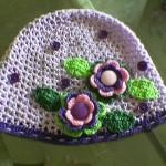 beyaz şapka mor pembe yeşil çiçek motifleri ile süslenmiş